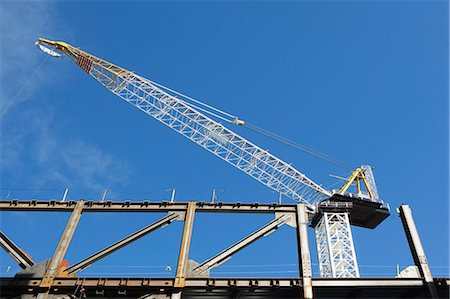 Low angle view of crane at construction site Stock Photo - Premium Royalty-Free, Code: 614-06537434