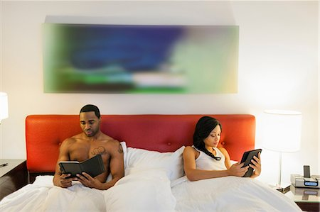 entertainment - Couple using e-readers in bed Stock Photo - Premium Royalty-Free, Code: 614-06537446