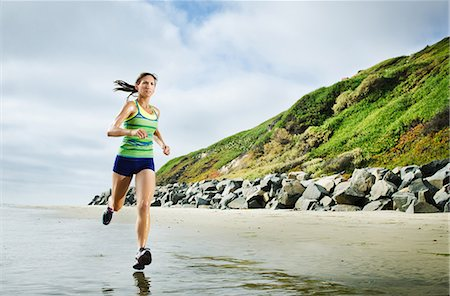 Woman running on beach Stock Photo - Premium Royalty-Free, Code: 614-06537470