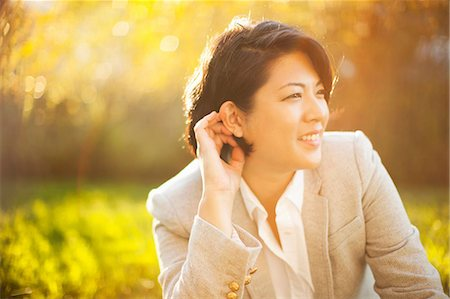 portrait looking away - Smiling businesswoman sitting outdoors Stock Photo - Premium Royalty-Free, Code: 614-06537504