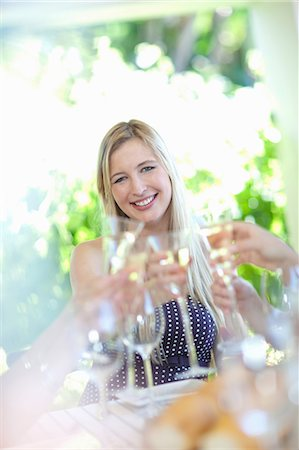 self indulgence - Woman toasting with champagne at table Stock Photo - Premium Royalty-Free, Code: 614-06537618