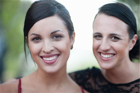 sister - Women smiling together outdoors Stock Photo - Premium Royalty-Free, Code: 614-06624003