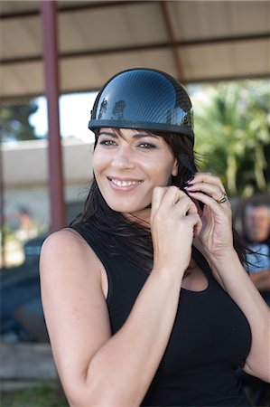 safety - Woman tying on scooter helmet Stock Photo - Premium Royalty-Free, Code: 614-06624132