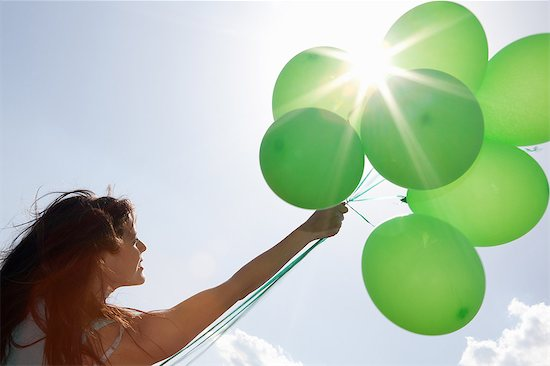 Woman carrying bunch of balloons Stock Photo - Premium Royalty-Free, Image code: 614-06624154