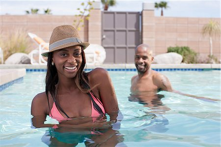Smiling couple sitting in pool Stock Photo - Premium Royalty-Free, Code: 614-06624306