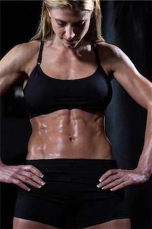 Sweating woman admiring her abs Stock Photo - Premium Royalty-Free, Code: 614-06624312