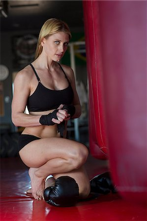 Boxer wrapping her hands in gym Stock Photo - Premium Royalty-Free, Code: 614-06624327