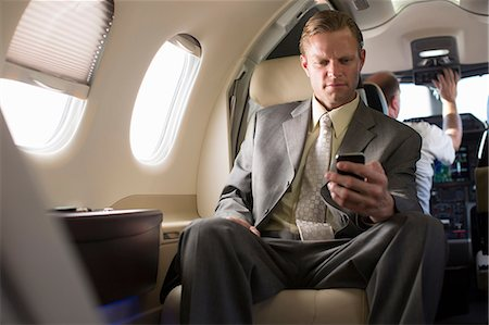 Businessman using cell phone on airplane Stock Photo - Premium Royalty-Free, Code: 614-06624348