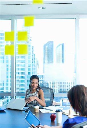 Businesswomen talking at desk Stock Photo - Premium Royalty-Free, Code: 614-06624390