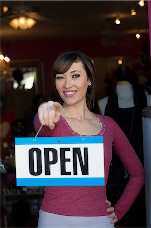 sign - Woman holding open sign in store Stock Photo - Premium Royalty-Free, Code: 614-06624465