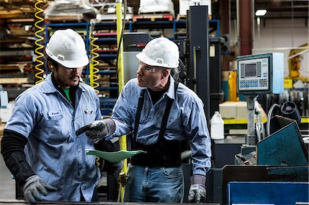 production - Workers talking in metal plant Stock Photo - Premium Royalty-Free, Code: 614-06624497