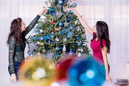 Teenage girls decorating Christmas tree Stock Photo - Premium Royalty-Free, Code: 614-06624582