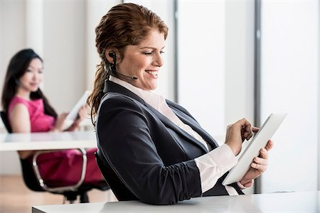 Businesswoman using tablet computer Stock Photo - Premium Royalty-Free, Code: 614-06624628