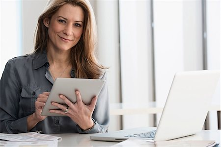 Businesswoman using tablet computer Stock Photo - Premium Royalty-Free, Code: 614-06624651