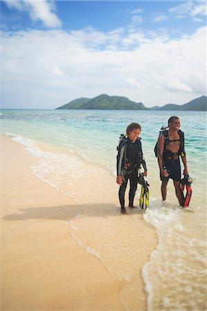 Scuba divers walking on tropical beach Stock Photo - Premium Royalty-Free, Code: 614-06624859