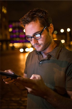 Man using tablet computer on city street Stock Photo - Premium Royalty-Free, Code: 614-06625025
