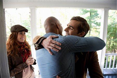 Men hugging at front door Stock Photo - Premium Royalty-Free, Code: 614-06625048