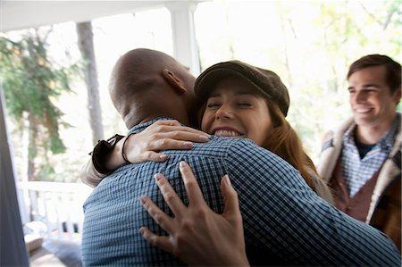 Friends hugging at front door Stock Photo - Premium Royalty-Free, Code: 614-06625049