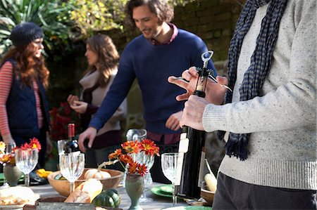 Man uncorking bottle of wine at table Stock Photo - Premium Royalty-Free, Code: 614-06625069