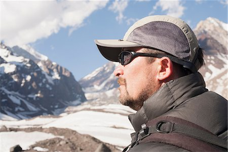 dark glasses - Hiker overlooking snowy mountains Stock Photo - Premium Royalty-Free, Code: 614-06625120
