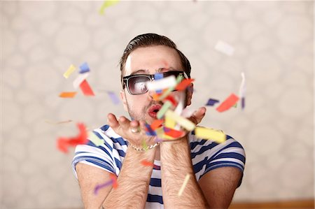 Man blowing confetti at party Stock Photo - Premium Royalty-Free, Code: 614-06625155