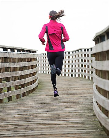 Woman running on wooden dock Stock Photo - Premium Royalty-Free, Code: 614-06625314