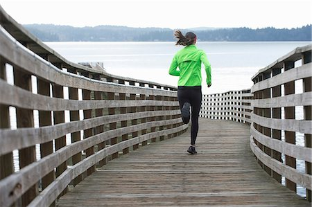 Woman running on wooden dock Stock Photo - Premium Royalty-Free, Code: 614-06625319