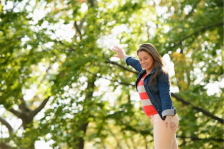 Smiling woman playing in park Stock Photo - Premium Royalty-Free, Code: 614-06625364