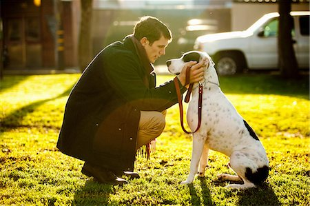 Man petting dog in park Stock Photo - Premium Royalty-Free, Code: 614-06625425