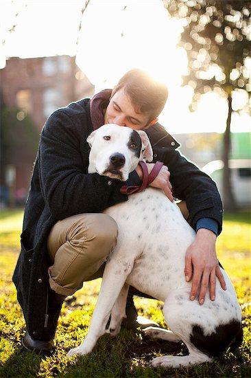 Man hugging dog in park Stock Photo - Premium Royalty-Free, Image code: 614-06625427