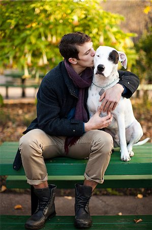 Man petting dog on park bench Stock Photo - Premium Royalty-Free, Code: 614-06625434