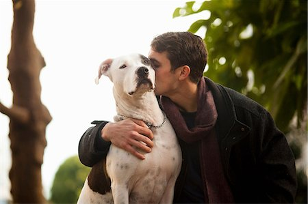 Man kissing dog outdoors Stock Photo - Premium Royalty-Free, Code: 614-06625436