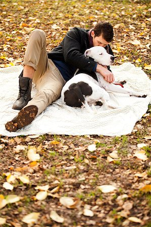 dog kissing man - Man and dog relaxing on picnic blanket Stock Photo - Premium Royalty-Free, Code: 614-06625439