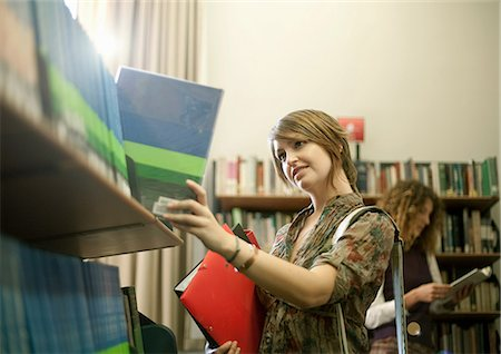 selecting - Student searching for book in library Stock Photo - Premium Royalty-Free, Code: 614-06623338