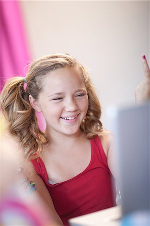 preteen girl pigtails - Smiling girl using laptop Stock Photo - Premium Royalty-Free, Code: 614-06623444