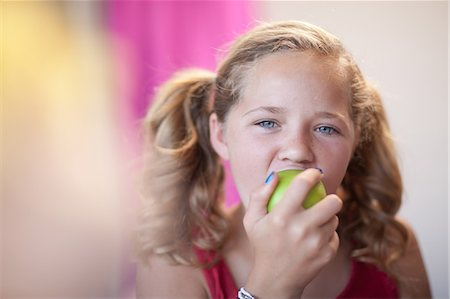 preteen girl pigtails - Close up of girl eating apple Stock Photo - Premium Royalty-Free, Code: 614-06623447
