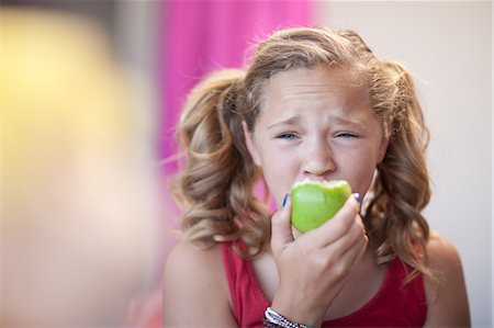 preteen girl pigtails - Close up of girl eating apple Stock Photo - Premium Royalty-Free, Code: 614-06623448