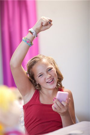 preteen girl pigtails - Cheering girl using cell phone Stock Photo - Premium Royalty-Free, Code: 614-06623441