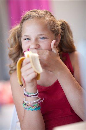 preteen girl pigtails - Smiling girl eating banana Stock Photo - Premium Royalty-Free, Code: 614-06623450