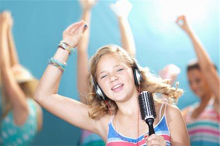 Girl singing into hairbrush Stock Photo - Premium Royalty-Free, Code: 614-06623491