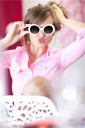 Teenage girl in sunglasses making face Stock Photo - Premium Royalty-Free, Code: 614-06623542