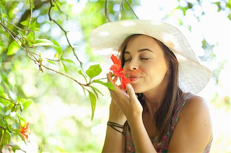smelling - Woman smelling flower in park Stock Photo - Premium Royalty-Free, Code: 614-06623588