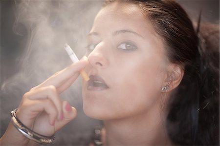 Teenage girl in dark makeup smoking Stock Photo - Premium Royalty-Free, Code: 614-06623595