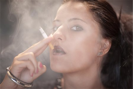 Teenage girl in dark makeup smoking Stock Photo - Premium Royalty-Free, Code: 614-06623595