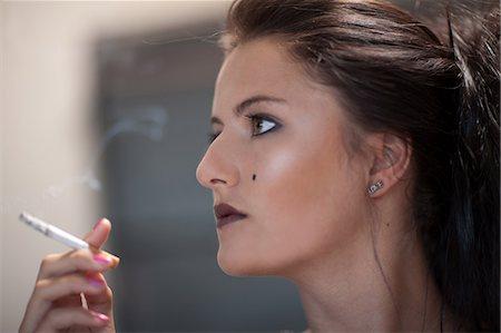 Teenage girl in dark makeup smoking Stock Photo - Premium Royalty-Free, Code: 614-06623598