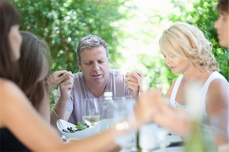 Family saying grace before eating Stock Photo - Premium Royalty-Free, Code: 614-06623604