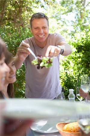 reaching - Man serving salad at table outdoors Stock Photo - Premium Royalty-Free, Code: 614-06623606