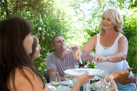 Woman serving salad at table outdoors Stock Photo - Premium Royalty-Free, Code: 614-06623608