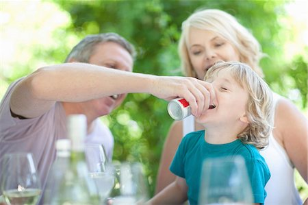 Father giving son soda at table Stock Photo - Premium Royalty-Free, Code: 614-06623616