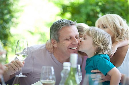 Boy kissing father at table outdoors Stock Photo - Premium Royalty-Free, Code: 614-06623612